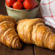 Croissants and bowl with ripe strawberries — Stock Photo #74384273