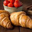 Croissants and bowl with ripe strawberries — Stock Photo #74384307