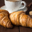Croissants and cup of coffee cappucino on dark brown wooden table, close up — Stock Photo #74384325