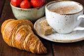Croissant, strawberries and cup of coffee — Stock Photo