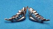 Silver earring as butterfly wings on blue — ストック写真