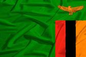 Zambia flag on a silk drape waving — Stock Photo