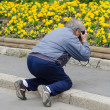 Old man taking picture of flowers on knees — Stock Photo #62915909
