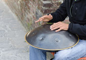 Man play instrument made of metal and called hang — Foto de Stock
