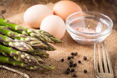 Fresh asparagus and eggs on a wooden table ready for omelette — Stock Photo