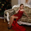 Fashionable woman is sitting near the Christmass tree in red dress — Stock Photo #59770153