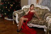 ファッショナブルな女性は赤いドレスの人工クリスマス ツリーのそばに座ってください。 — ストック写真
