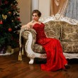 Fashionable woman is sitting near the Christmass tree in red dress — Stock Photo #60273829