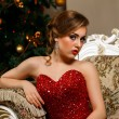 Fashionable woman is sitting near the Christmass tree in red dress — Stock Photo #60328717