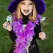 Little beautiful girl with halloween witch costume eating candy and showing purple tongue — Stock Photo #55501475
