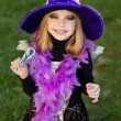 Little beautiful girl with halloween witch costume smiling and have colored candy — Stock Photo #55501487