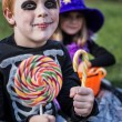 Red haired boy wearing halloween skeleton costume and holding colorful candies — Stock Photo #55501507