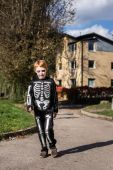 Little red haired boy wearing halloween skeleton costume — Stock Photo