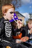 Red haired child with skeleton costume eating colorful candy. Halloween — Stock Photo