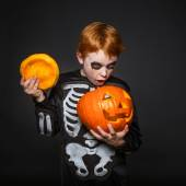 Surprised red haired boy in skeleton costume holding a orange pumpkin. Halloween — Stock Photo
