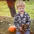 Autumn. Beautiful smiling blond boy holds a leaf — Stock Photo #55681115
