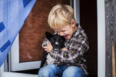 Beautiful blond child embrace his dog. Friendship between human and animal — Стоковое фото