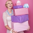 Laughing blonde woman holding big and small colorful gift boxes. Soft colors. Christmas, birthday, Valentine day, presents — Stock Photo #58501625