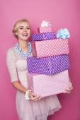 Laughing blonde woman holding big and small colorful gift boxes. Soft colors. Christmas, birthday, Valentine day, presents — Stock Photo