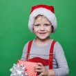 Smiling funny child in Santa red hat. Holding Christmas gift in hand. Christmas concept — Photo #59264439