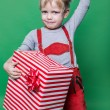 Kid in red costume of dwarf holding Christmas gift and throws Santa Claus cap. Naughty child — Stock Photo #59264447
