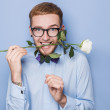 Attractive young man smiling with a white rose in his mouth. Date, birthday, Valentine — Stock Photo #61520603