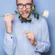 Attractive young man smiling with a white rose in his mouth. Date, birthday, Valentine — Stock Photo #61520605
