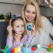 Young mother and her beautiful daughter painting Easter eggs — Stock Photo #67921127