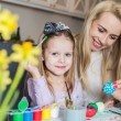 Young mother and her beautiful daughter painting Easter eggs — Stock Photo #67921131