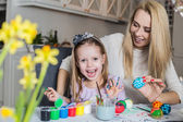 Happy mother and daughter painting easter eggs in the living room — Stock Photo