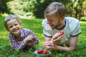 Summer photo happy father and son together lying on green grass. Life moment family resting on the nature — Stock Photo