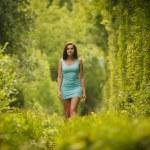 Beautiful girl walking through nature tunnel — Stock Photo #77632004