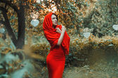 Beautiful girl in a red dress standing in the garden with hearts — Stockfoto
