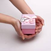 Women's hands holding a pink gift with a note I love you. — Stock Photo