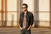 Portrait of a young man in a black leather jacket and sunglasses — Stockfoto