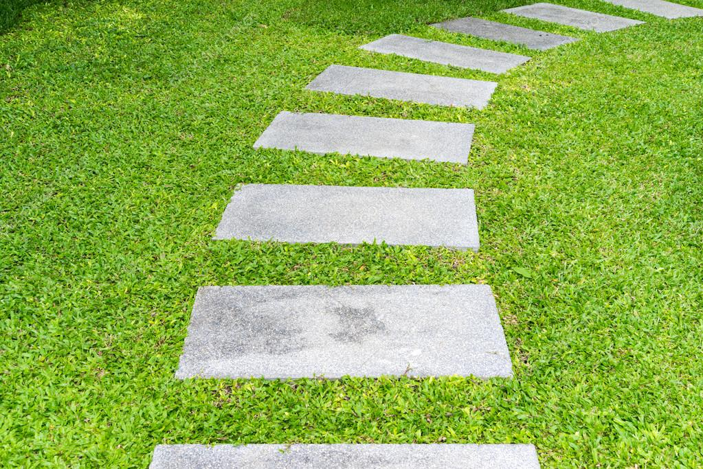 pedra cimento jardim:Passarela de pedra de jardim entre gramíneas — Fotografias de Stock