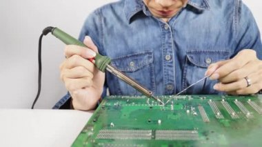 Expert technician are repairing solder weld, fuse together by heating a lead to melt at the back of motherboard — Stock Video