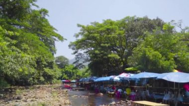 NAKHON NAYOK, THAILAND - APRIL 4 2015 : Tourists enjoy a special restaurant that have beautiful atmosphere near waterfall stream, everyone have a chance to get feet inside the stream while eating — Stock Video