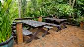 Wooden chairs and table set at balcony in a green plant garden. — Stok fotoğraf