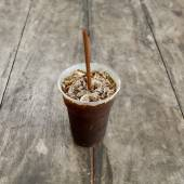 Delicious ice coffee americano on old wood table. — Stock Photo