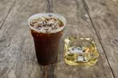 Delicious ice coffee americano  with cigarette on the old wooden — Stock Photo