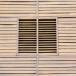 Closed wooden shutters on a wooden panneled wall. — Stock Photo #64886037
