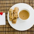 A cup of white coffee and chocolate chip cookies with notepad an — Stock Photo #65223787