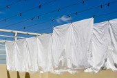 White clothes hanging on the line against blue sky. — Stock Photo