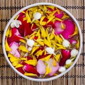 Water with jasmine and roses corolla in bowl — Stock Photo
