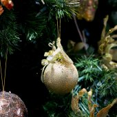 Stripy christmas ball, cristmas tree in the background — Stock Photo