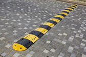 Traffic safety speed bump on an asphalt road — Stock Photo
