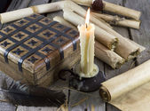 Still life with box, candle and scrolls — Stock Photo