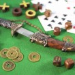Decorated knife with golden ancient coins and playing cards on green background — Stock Photo #54586809