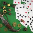 Decorated knife with golden ancient coins and playing cards on green background — Stock Photo #54586813